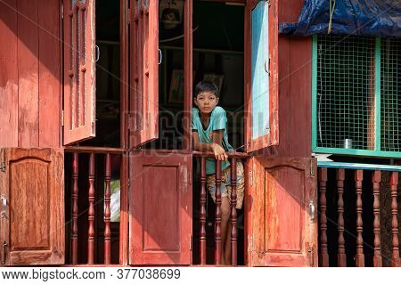 Mon State, Myanmar - December 30, 2019: View Of A Young Boy Looking From The Window Of His House In