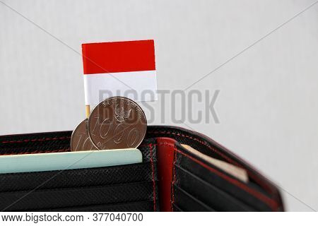 Two Coins Of One Thousand Rupiah With Mini Indonesia Flag Stick On The Black Wallet On White Backgro