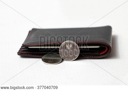 Two Coins Of One Thousand Indonesia Rupiah With Black Wallet On White Floor. Concept Of Finance Or C