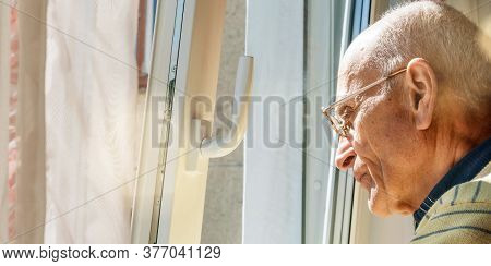 Bald Old Man In Glasses Stands At Window With Open Vent Looking Outside Under Bright Summer Morning