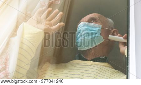 Pensioner In Yellow Pullover And Blue Disposable Mask Stands By Window Waving Hand Close Low Angle S
