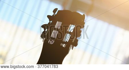 Acoustic Guitar Headstock And Metal Machine Heads Silhouettes Against Blurry Window Behind White Cur