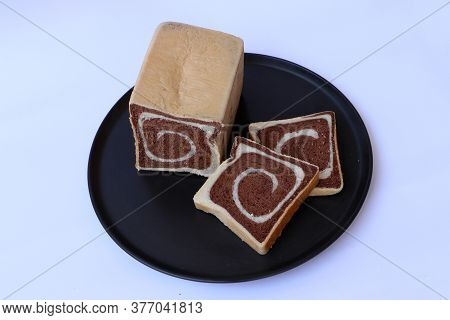 Two Tone Bread Chocolate In The Black Round Plate On The White Base.