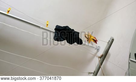 Black Wet Tights Hang On Exhaust Dryer Near Coloured Clothespins Under White Ceiling In Bathroom Clo
