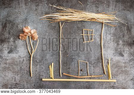 House Made With Sprigs Of Plants On Gray Background