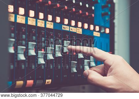 Close-up Hand Adjust The Volume On Sound Mixer In Studio Workplace For Live The Media And Sound Reco