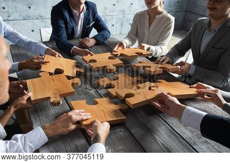 Business People Team Sitting Around Meeting Table And Assembling Wooden Jigsaw Puzzle Pieces Unity C