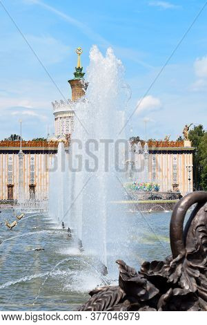 Moscow, Russia - July 2, 2020: Fountain Jets Against The Stone Flower Fountain And Ukraine Pavilion