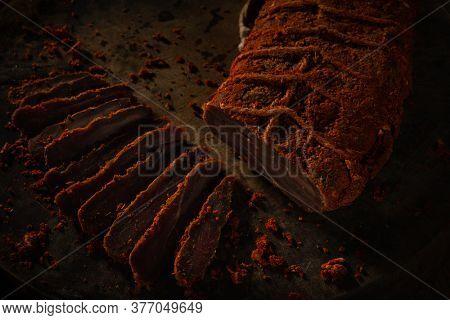 Basturma, dried tenderloin of beef meat, jerky, thinly sliced.  Beef jerky, bresaola, dried beef - Basturma in Red Pepper on a dark wooden background.