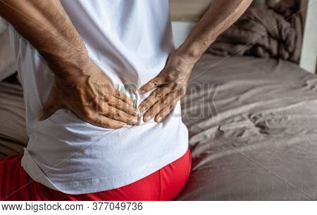 Back View Of The Young Man With Back Pain Sitting On The Bed At Home