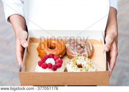 Close Up Hands Holding Four Pieces Of Totally Different Colorful And Delicious Looking Donuts In Eco