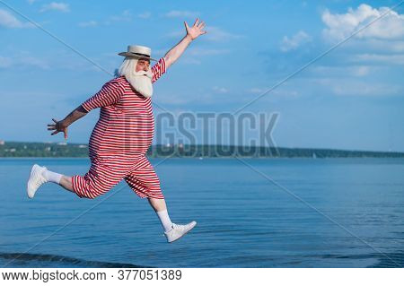 An Elderly Man In A Striped Retro Swimsuit Runs And Jumps Along The Beach. A Cheerful Gray-haired Ol