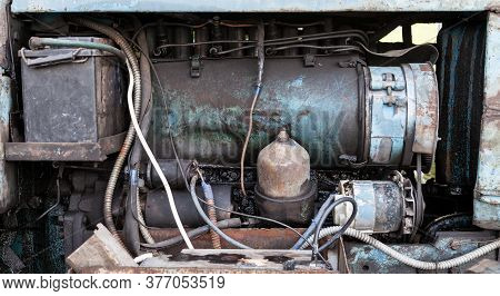 Close-up On An Old Rusty Tractor Or Truck Engine With A Battery And Oil Drips During Repair In A Wor