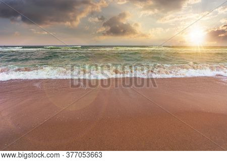 Sandy Beach And Turquoise Sea At Sunset. Great View Of Waves Rolling To The Coastline. Wonderful Wea