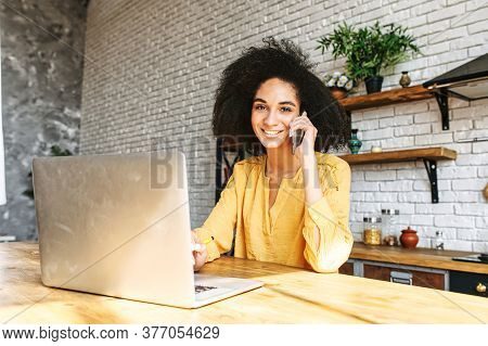 Midshot Of An Attractive Afro-american Girl Taking On The Phone With A Laptop In Front Of Her. She L