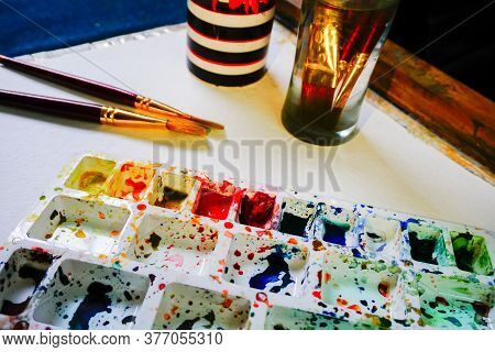 An Watercolour Artists Desk With Watercolour Palette, Brushes, Glass Of Water And Flowers. Vibrant C