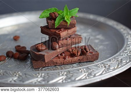 Pieces Of Dark Chocolate And A Sprig Of Mint On A Silver Tray.