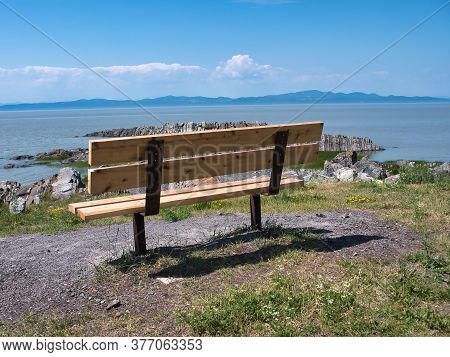 Lonely Park Bench Overlooking The Ocean In Quebec, Canada