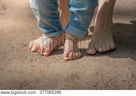 The First Steps, The Little Feet Of The Baby Walk Barefoot On The Sand, The Child Learns To Walk
