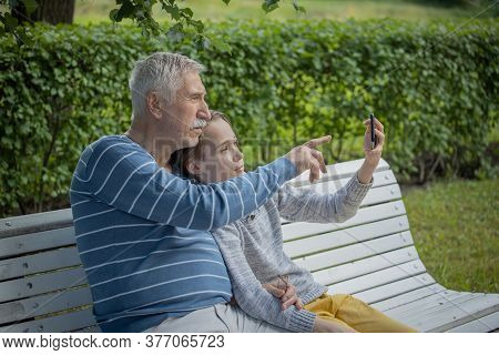 Portrait Of A Boy And Grandfather, Happy, Cheerful Grandfather And Grandson With Smartphone Taking S