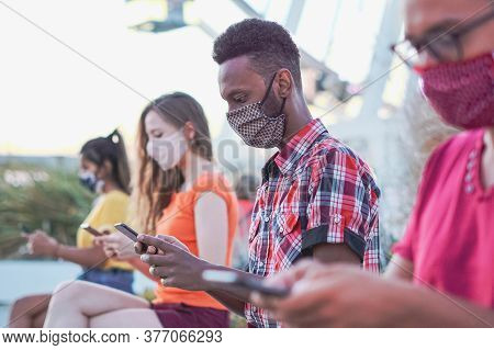 Friends Using Their Smartphones In Covid 19 Times Protected With Face Mask -  Young People Using Mob