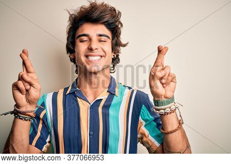 Young man on vacation wearing summer colorful shirt standing over isolated white background gesturing finger crossed smiling with hope and eyes closed. Luck and superstitious concept.