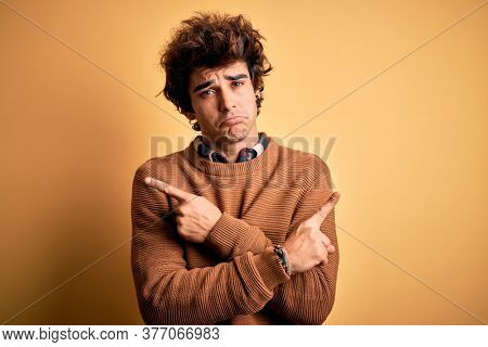 Young handsome man wearing casual shirt and sweater over isolated yellow background Pointing to both sides with fingers, different direction disagree