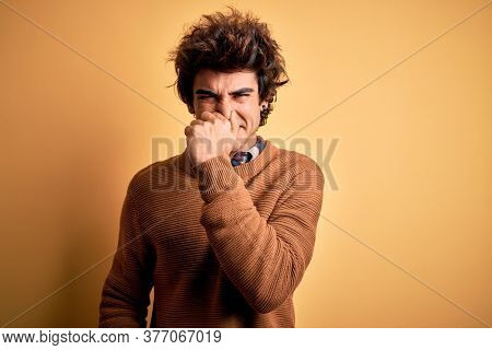 Young handsome man wearing casual shirt and sweater over isolated yellow background smelling something stinky and disgusting, intolerable smell, holding breath with fingers on nose. Bad smell