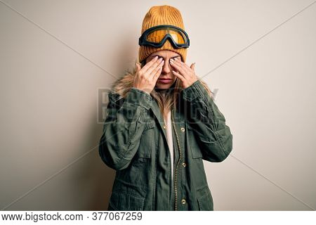 Young brunette skier woman wearing snow clothes and ski goggles over white background rubbing eyes for fatigue and headache, sleepy and tired expression. Vision problem