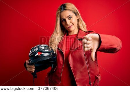 Young beautiful blonde motorcyclist woman holding moto helmet over isolated red background with angry face, negative sign showing dislike with thumbs down, rejection concept