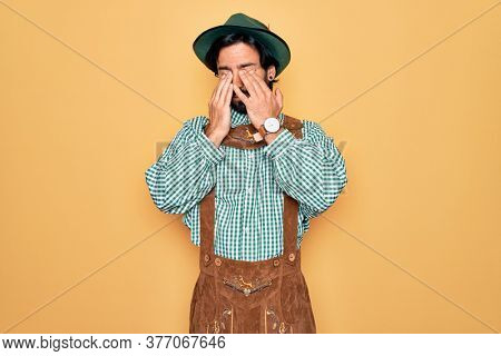 Young handsome man wearing tratidional german octoberfest custome for Germany festival rubbing eyes for fatigue and headache, sleepy and tired expression. Vision problem