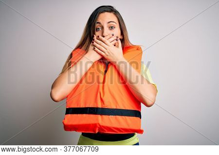 Young beautiful blonde woman with blue eyes wearing orange lifejacket over white background shocked covering mouth with hands for mistake. Secret concept.