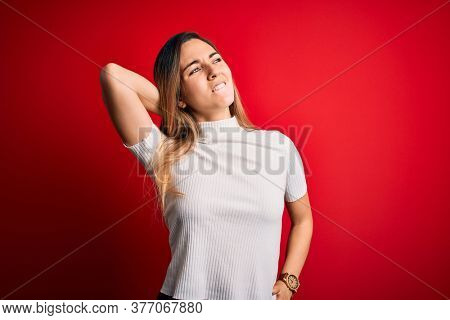 Beautiful blonde woman with blue eyes wearing casual white t-shirt over red background Suffering of neck ache injury, touching neck with hand, muscular pain