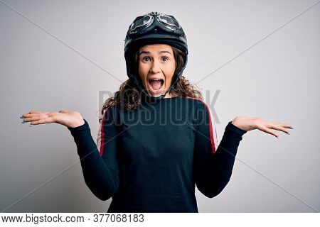 Beautiful motorcyclist woman with curly hair wearing moto helmet over white background celebrating crazy and amazed for success with arms raised and open eyes screaming excited. Winner concept