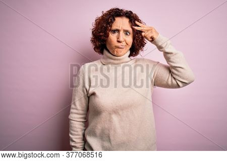 Middle age beautiful curly hair woman wearing casual turtleneck sweater over pink background worried and stressed about a problem with hand on forehead, nervous and anxious for crisis