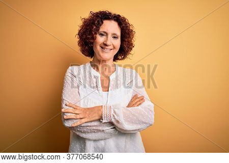 Middle age beautiful curly hair woman wearing casual summer dress over yellow background happy face smiling with crossed arms looking at the camera. Positive person.