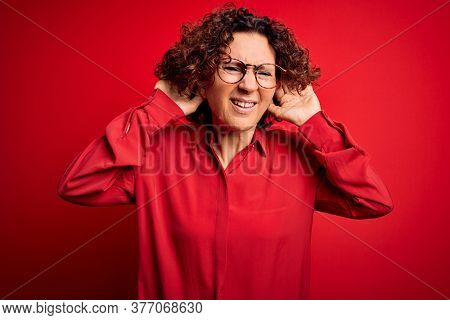 Middle age beautiful curly hair woman wearing casual shirt and glasses over red background Trying to hear both hands on ear gesture, curious for gossip. Hearing problem, deaf