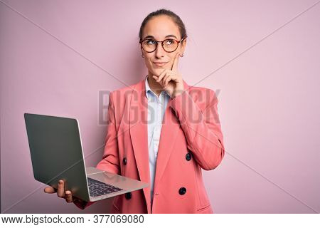 Young beautiful businesswoman wearing glasses working using laptop over pink background serious face thinking about question, very confused idea
