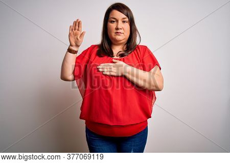 Beautiful brunette plus size woman wearing casual red t-shirt over isolated white background Swearing with hand on chest and open palm, making a loyalty promise oath