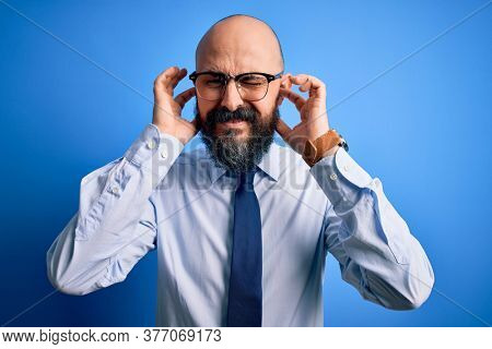 Handsome business bald man with beard wearing elegant tie and glasses over blue background covering ears with fingers with annoyed expression for the noise of loud music. Deaf concept.