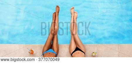 Top View Of Young Female Friends Sunbathing By Poolside With Fresh Cocktails, Closeup Of Legs. Copy