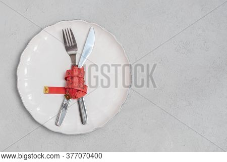 Fork And Knife With Red Measuring Tape On White Plate. Diet And Loose Weight Concept