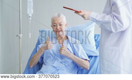 Happy Woman Doctor Talking And Using Tablet To Sick Old Female Senior Elderly Patient Lying In Bed I