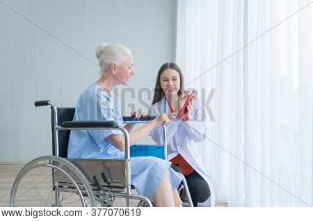 Happy Woman Doctor Talking To Disabled Old Female Senior Elderly Patient On Wheelchair In Hospital W