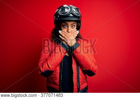 Young african american motorcyclist girl wearing moto helmet and glasses over red background shocked covering mouth with hands for mistake. Secret concept.