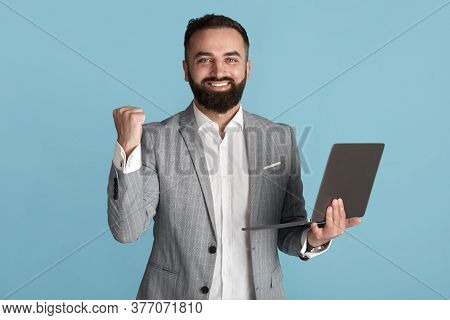 Joyful Corporate Executive With Laptop Gesturing Yes In Triumph Over Blue Background