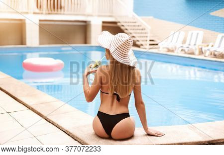 Back View Of Young Girl In Straw Hat Sitting At Poolside And Drinking Summer Cocktail, Outside