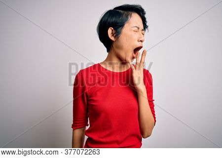 Young beautiful asian women wearing casual red t-shirt standing over isolated white background bored yawning tired covering mouth with hand. Restless and sleepiness.
