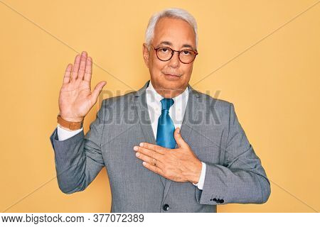 Middle age senior grey-haired handsome business man wearing glasses over yellow background Swearing with hand on chest and open palm, making a loyalty promise oath