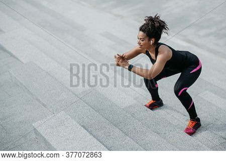 Jumping And Squats On Stairs. Smiling African American Girl With Wireless Headphones And Fitness Tra